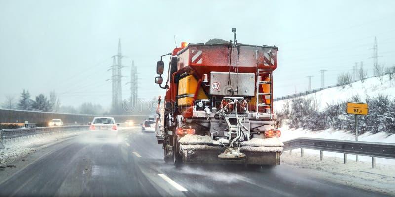 Den orange lastbilen för huvudvägunderhållsgritteren som fördelar de isläggning, saltar på vägen konditioneriner farlig körning royaltyfria foton