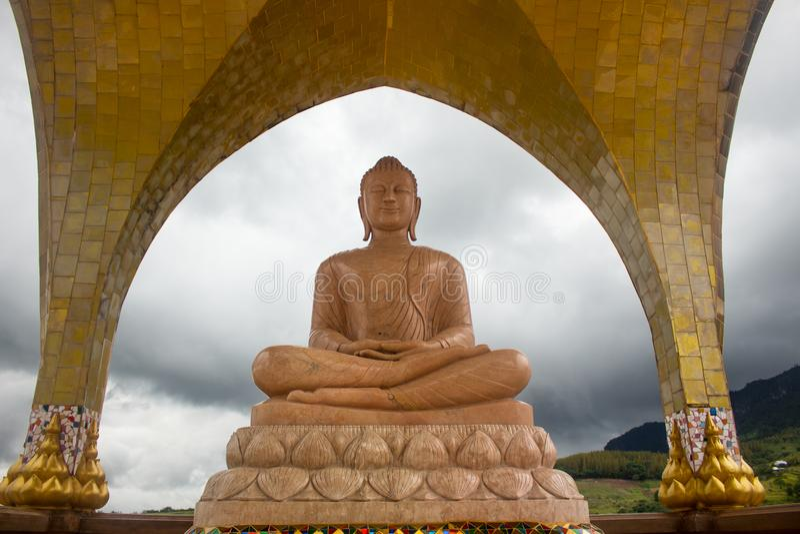 Den orange marmorbuddha statyn i meditation poserar royaltyfri foto