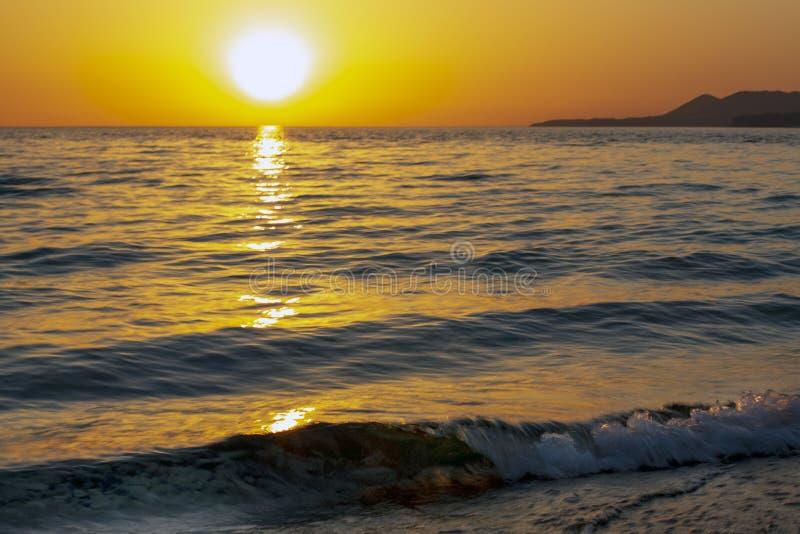 Den orange solnedgången över havet fotografering för bildbyråer