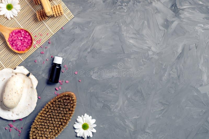 Den organiska brunnsortskönhetsmedlet och produkter på grå färger stenar bakgrund Skeden med det rosa badet saltar, kroppborsten, fotografering för bildbyråer