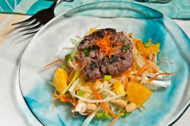 Den organiska kryddiga lammhamburgaren med den orange örtvitkålssalladen Paleo bantar arkivbild