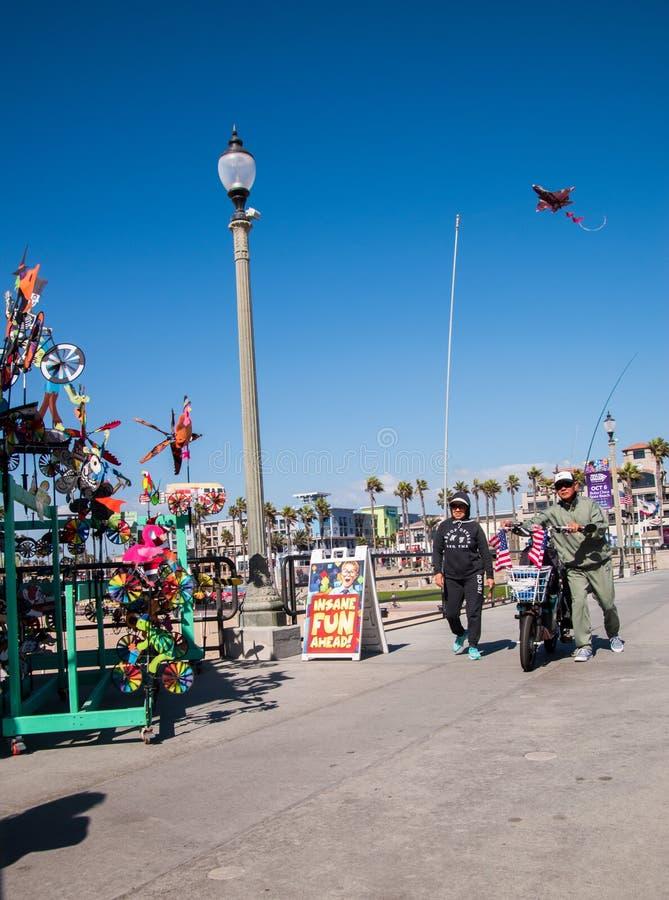 Den orientaliska mannen och kvinnan är sett gå på Huntington Beachpir förbi en ställning som säljer drakar och vindstifthjul Mann fotografering för bildbyråer