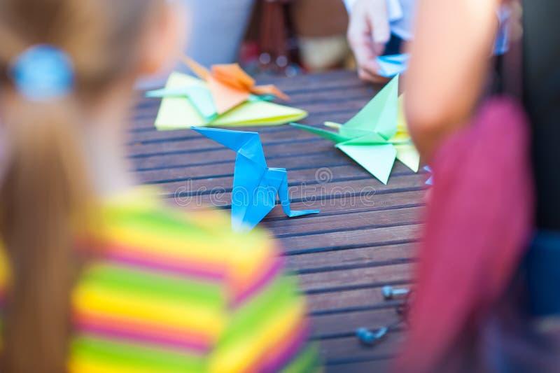 Den Origami, arbeitend mit farbigem Papier machend, formen Kinder vom Papier stockbild