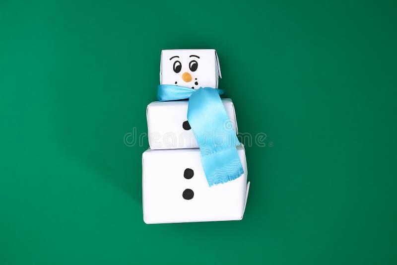 Den original- designen av gåvan för tre jul av vitbok, ett satängband i form av en snögubbe på en grön bakgrund royaltyfria bilder