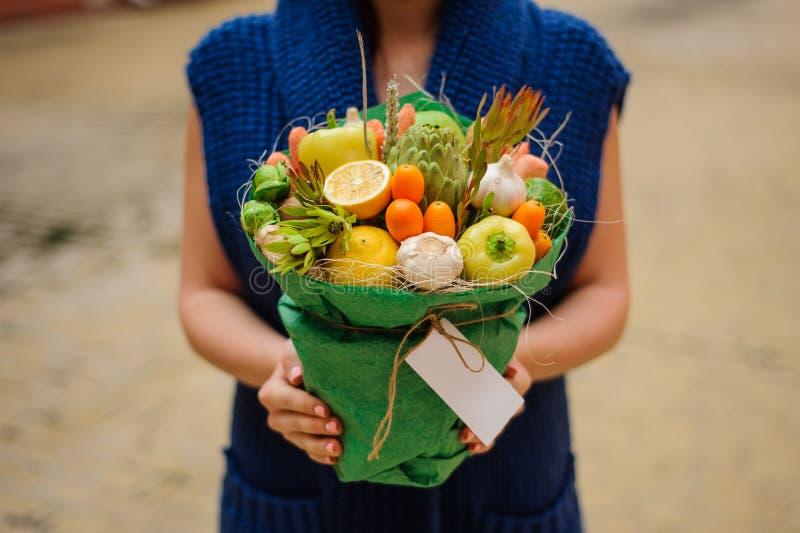 Den original- ovanliga ätliga grönsak- och fruktbuketten med kortet i kvinnahänder royaltyfria bilder