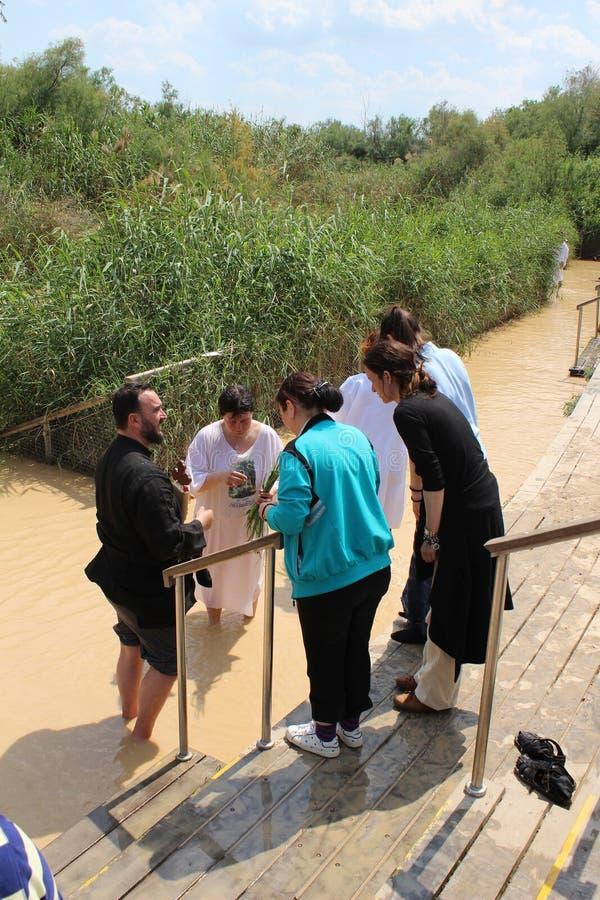 Den ortodoxa kristen vallfärdar som en del av en traditionell dopceremoni i Jordan River arkivbild