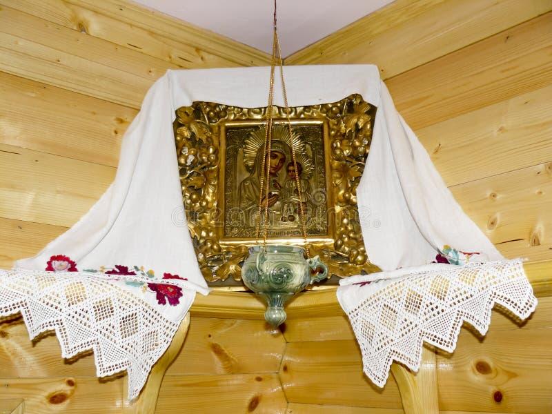 Den ortodoxa symbolen av modern av guden och Jesus med lampan i hörnet av rummet arkivfoto