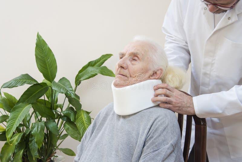 Den ortopediska kirurgen sätter på en vit ortopedisk krage av en mycket gammal kvinna som sitter på en stol royaltyfria foton