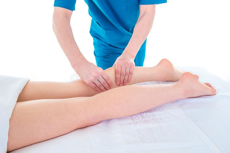 Den ortopediska kirurgen undersöker och masserar patientens ben i kliniken royaltyfria bilder