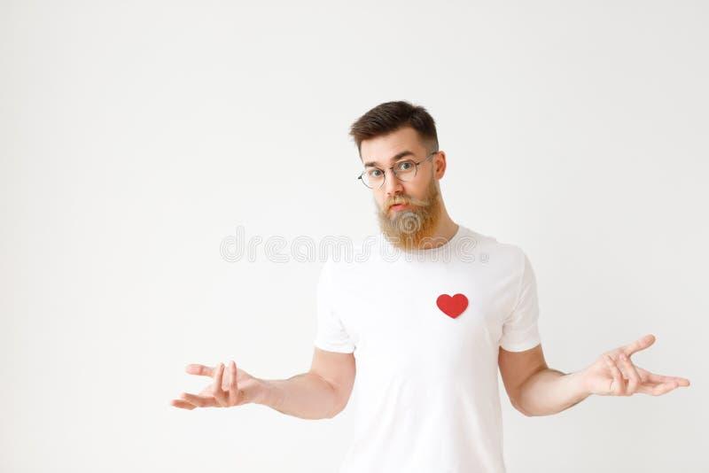 Den osäkra tveksamma skäggiga mannen i tillfälliga t-skjortashruggs knuffar i förvirring, försök att göra beslut om framtid royaltyfri fotografi
