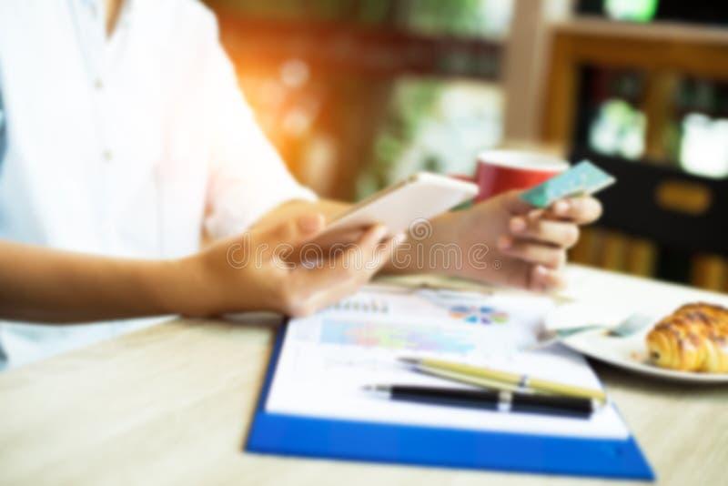 Den oskarpa ljusa designbakgrunden av damen använder mobiltelefonen för att shoppa direktanslutet fotografering för bildbyråer
