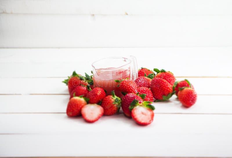 Den oskarpa ljusa designbakgrunden av jordgubbefruktsaft i plast- kopp royaltyfria foton