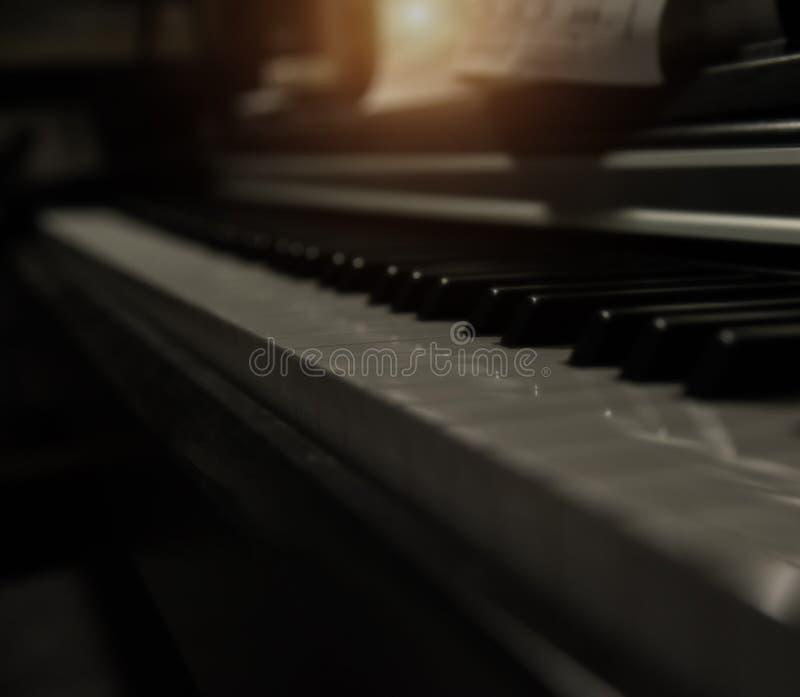 Den oskarpa ljusa designbakgrunden av pianotangenter, där är vita pianotangenter och svarta pianotangenter royaltyfri bild