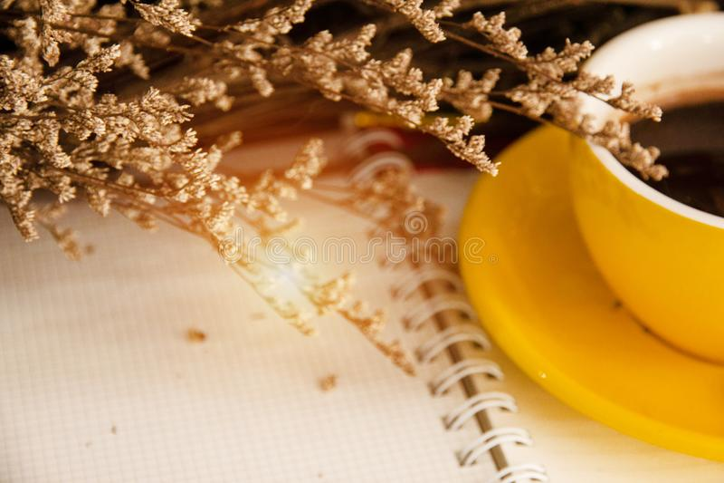 Den oskarpa ljusa designbakgrunden av den torkade blomman och halvan av gul keramisk bok, tappning och konst för kaffekopp pålagd fotografering för bildbyråer