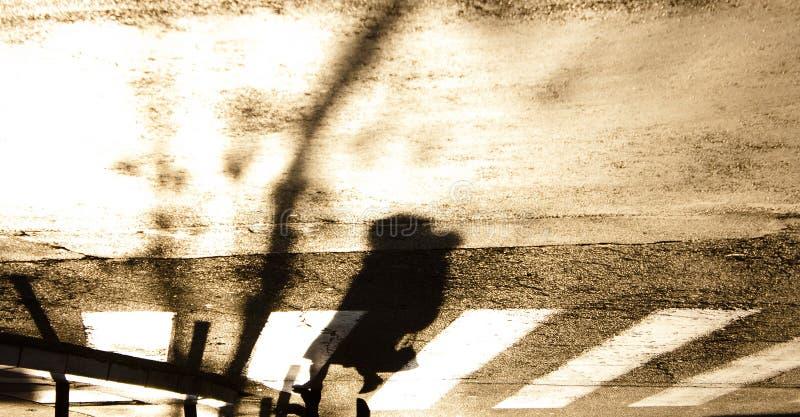 Den oskarpa zebramarkeringen med konturn och skugga av en kvinna går arkivbilder