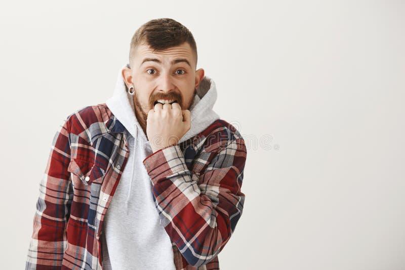 Den otrygga bekymrade grabben har lotter på hans mening Stickande näve för förskräckt nervös ung europeisk manlig hipster som sti royaltyfria bilder