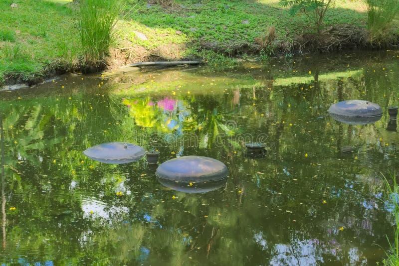 Den ovanliga intressanta samlingen av utrustning för vattenspringbrunn i en frodig gräsplan som är thailändsk parkerar kanalen arkivfoto