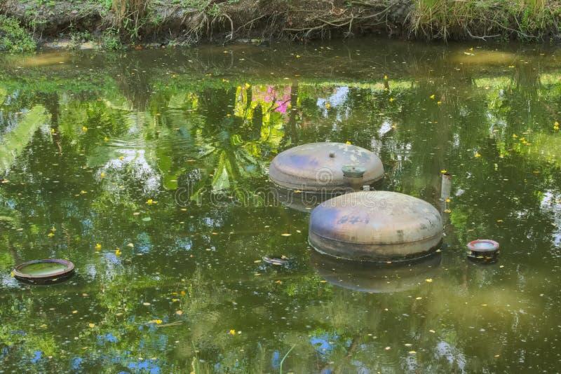 Den ovanliga intressanta samlingen av utrustning för vattenspringbrunn i en frodig gräsplan som är thailändsk parkerar kanalen royaltyfria bilder