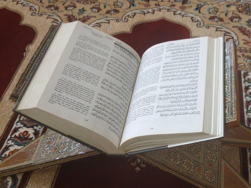 Den på engelska heliga quranen och arabiska på en härlig Östlig-modell utformad filt fotografering för bildbyråer