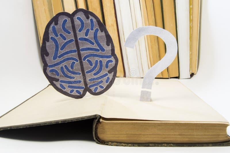 Den pappers- hjärnkonturn och frågefläcken är över den gamla öppna medicinska boken Foto som ser frågor och frågor i studie av hj royaltyfria foton
