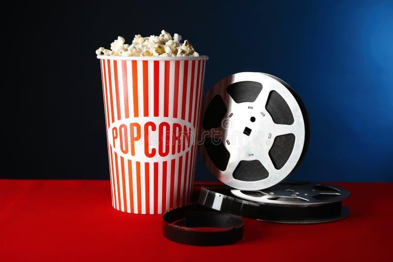 Den pappers- koppen med smakligt popcorn och filmen reel royaltyfri bild