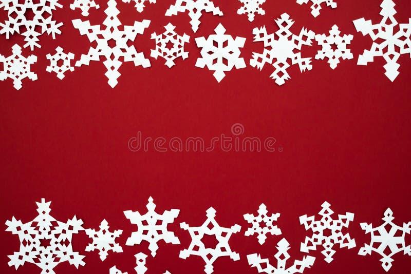 Den pappers- snön flagar på den röda bakgrunden Rött tema för jul royaltyfria bilder