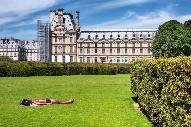 Den parisiska citylandscapen - den avslappnande unga mannen tar att solbada på gräsmattan den Tuileries trädgården bredvid Louvre arkivbild