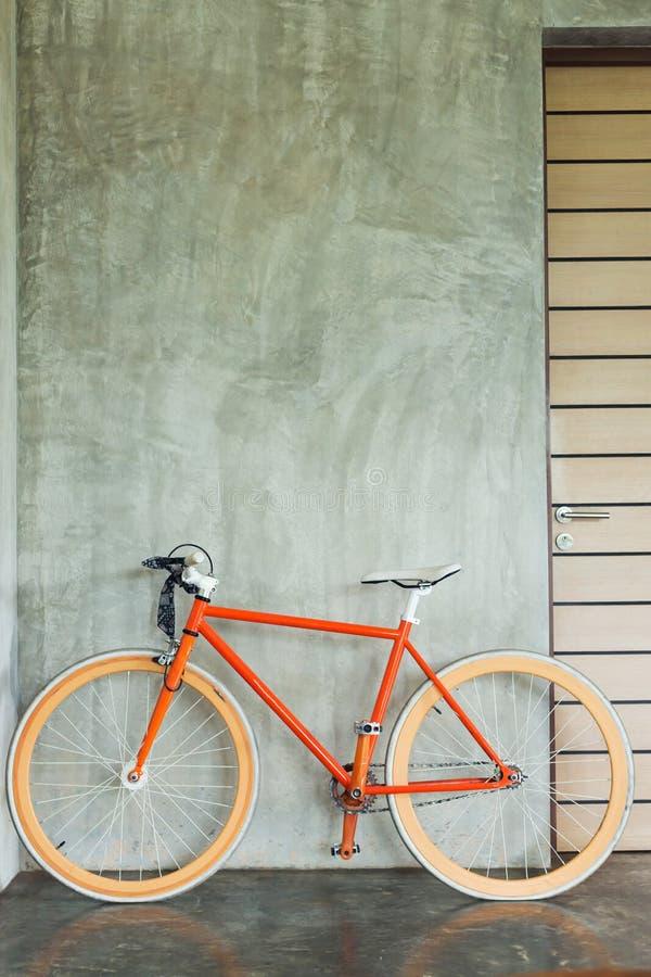 Den parkerade orange cykeln dekorerar modern stil för inre vardagsrum royaltyfria foton