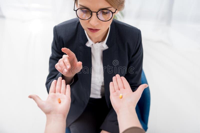 den partiska sikten av affärskvinnan som väljer mediciner från kollegor, räcker fotografering för bildbyråer