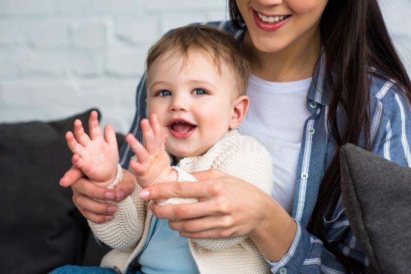den partiska sikten av att le modern som spelar med litet, behandla som ett barn fotografering för bildbyråer