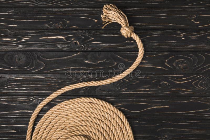 den partiska sikten av brunt knöt det nautiska repet som var ordnat i cirkel på träyttersida royaltyfri bild