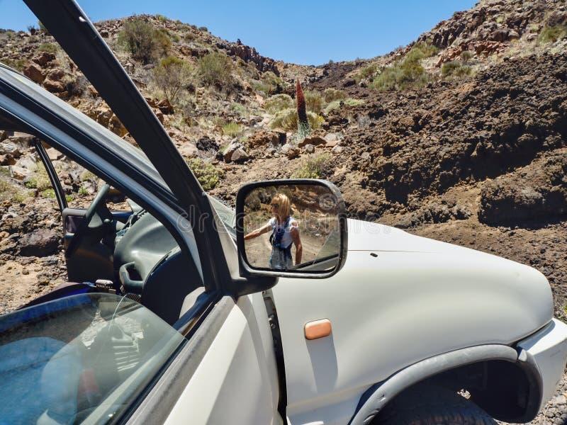 Den partiska sikten av en stor bil, i rätsidaspegeln är en kvinna som ser i bakgrunden den karga öknen royaltyfri foto