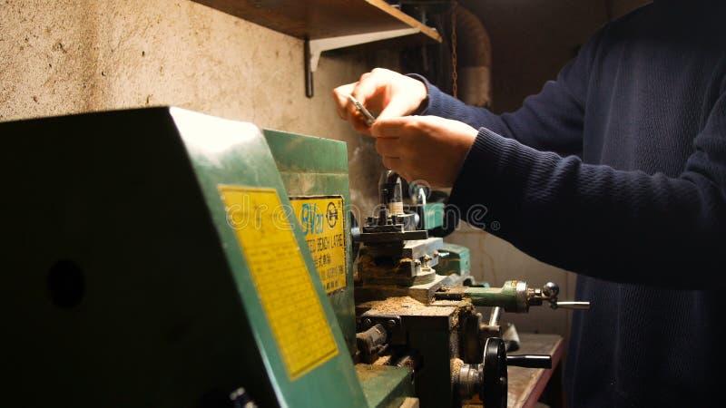 Den passionerade DIY-mannen, använder han drejbänken för DIY, i hans hem- laboratorium, precisionarbete med metalldrejbänken arkivfoton