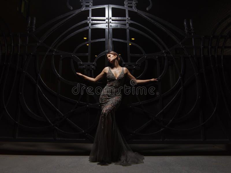 Den passionerade och attraktiva klädda unga kvinnan i en uttrycksfull mousserande aftonklänning poserar smartly på natten arkivfoton