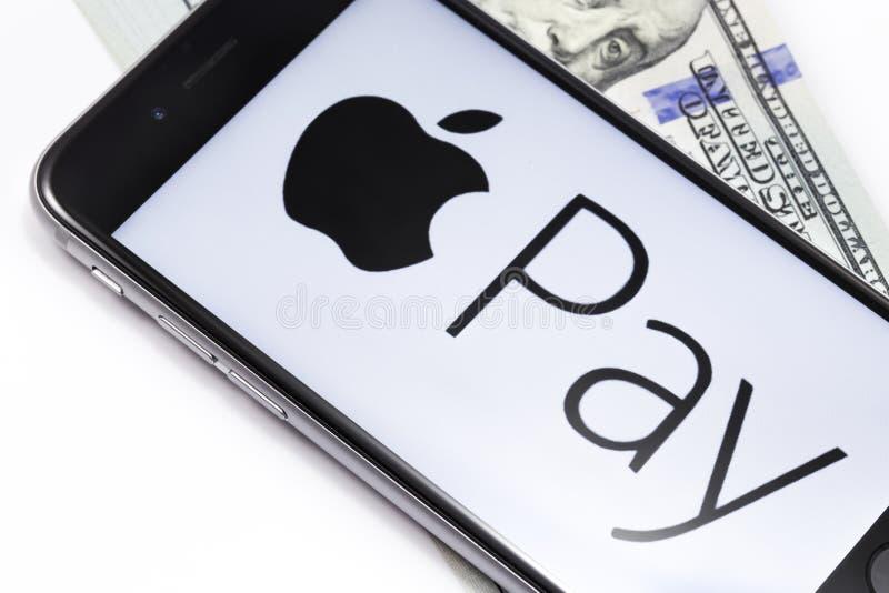 Den pengar- och Apple iPhonen 6s med Apple lön servar logo Ekaterinb arkivbilder