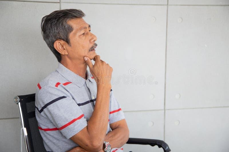 Den pensionärAsien affärsmannen sitter och att tänka arkivfoto