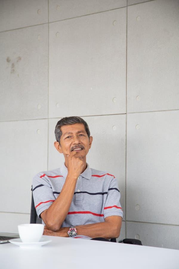 Den pensionärAsien affärsmannen sitter och ler arkivbild