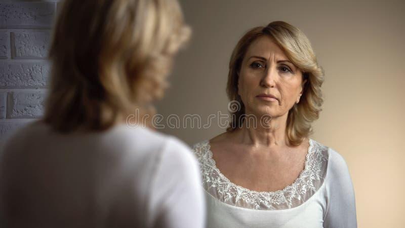 Den pensionerade kvinnan som ser SAD in i spegeln, utseendemässigt problem för ålder, rynkar royaltyfri fotografi