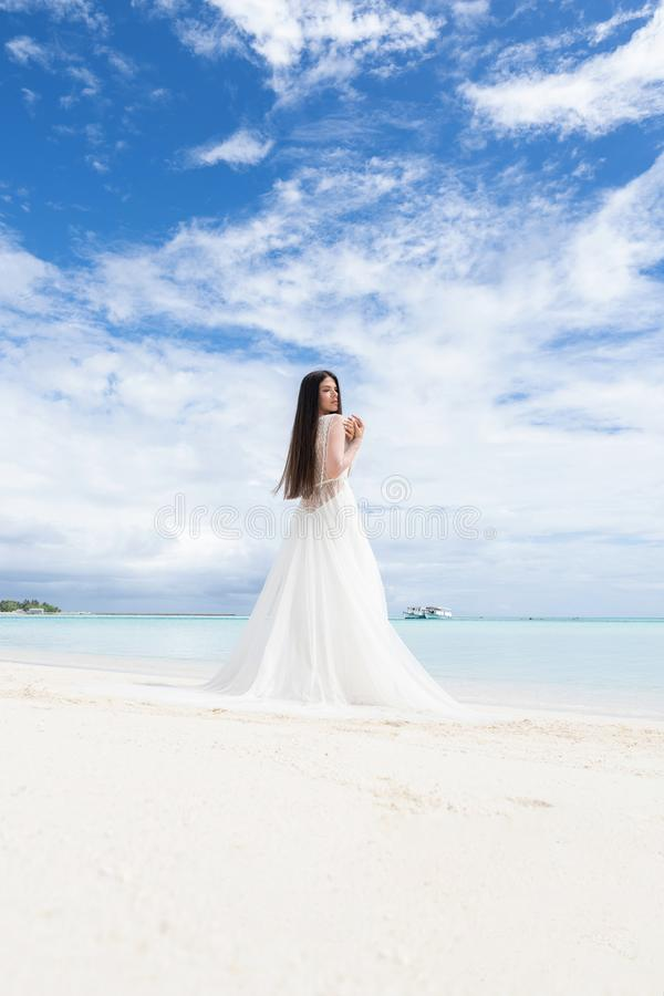 Den perfekta bruden En ung brud i en vit klänning står på en snövit strand royaltyfri bild