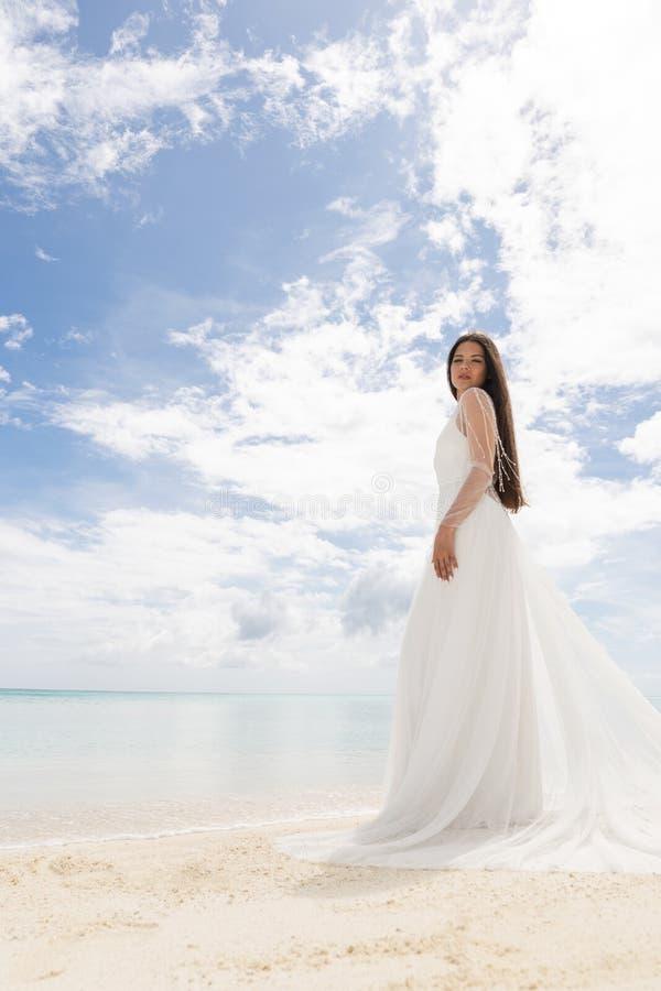 Den perfekta bruden En ung brud i en vit klänning står på en snövit strand royaltyfri foto