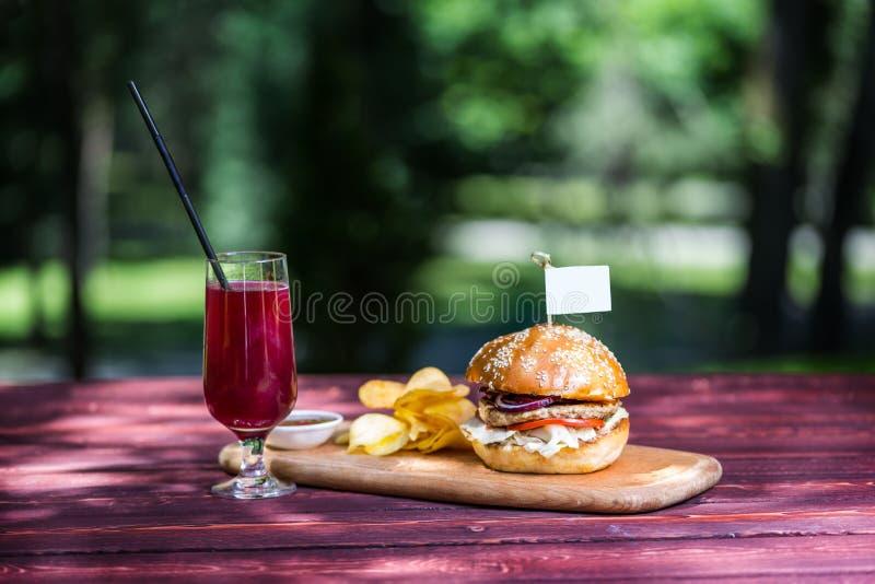 Den perfekta kötthamburgaren med chips och ny kall lemonad På skärbrädan och grön sommarbakgrund arkivfoto