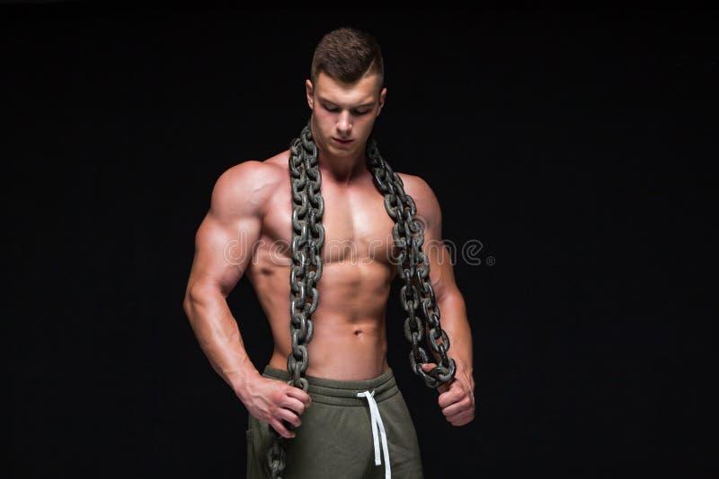 Den perfekta manliga kroppen - enormt posera f?r kroppsbyggare Rym en kedja bakgrund isolerad white kopiera avst?nd royaltyfri fotografi
