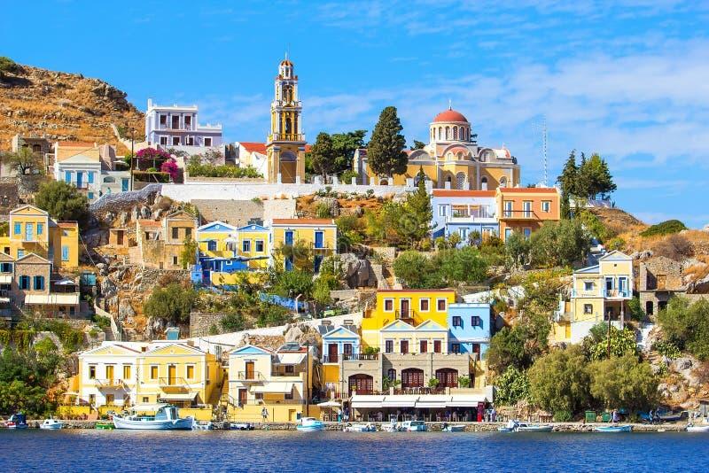 Den perfekta soliga dagen och den härliga sikten från havet på färgrika hus vaggar på på den grekiska ön Simi Symi, Dodecanesse arkivfoton