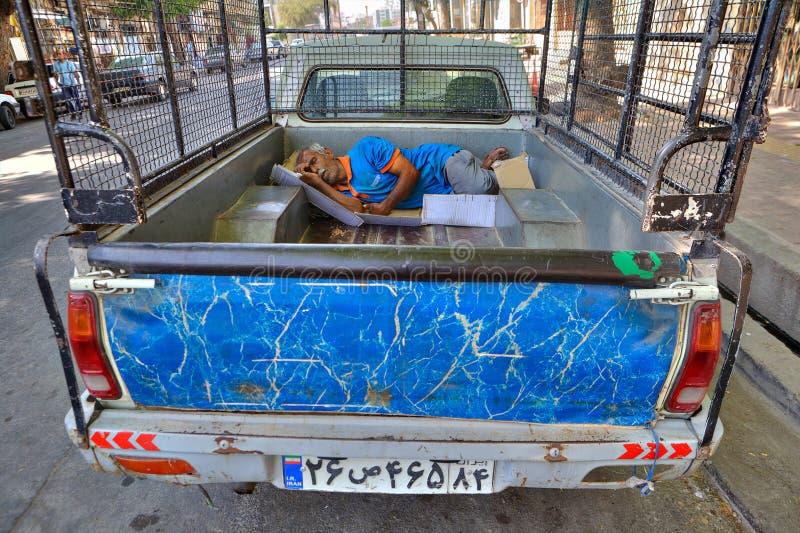 Den persiska arbetaren sover i baksidan av en lastbil utomhus arkivbild