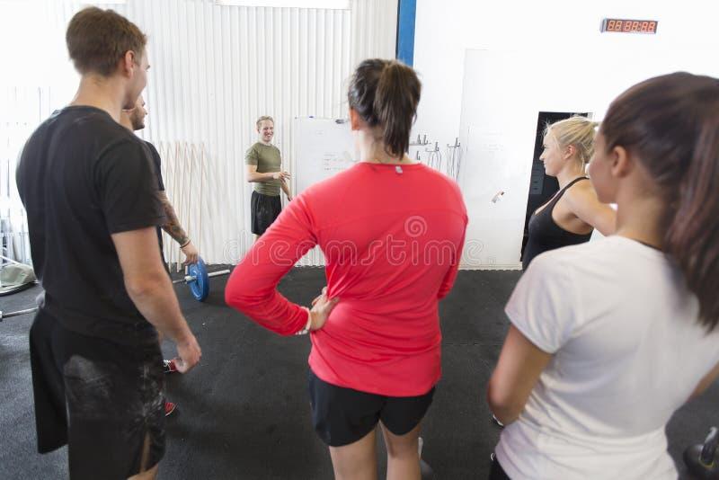 Den personliga instruktören instruerar hans konditiongenomkörarelag royaltyfri foto