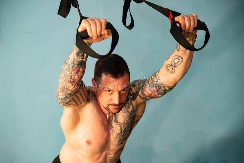 Den personliga instruktören med en tatuerad kropp gör genomköraren i idrottshallen arkivfoton