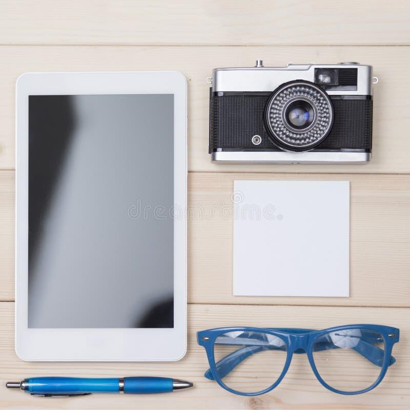 Den personliga saker sänker lekmanna- Digital minnestavla, bollpenna, glasögon, retro kamera och anteckningsbok royaltyfri foto