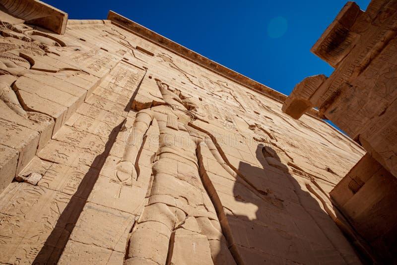 Den Philae tempelfasaden med jätten vaggar den sned statyn av Isis Goddess och hieroglyf royaltyfria bilder