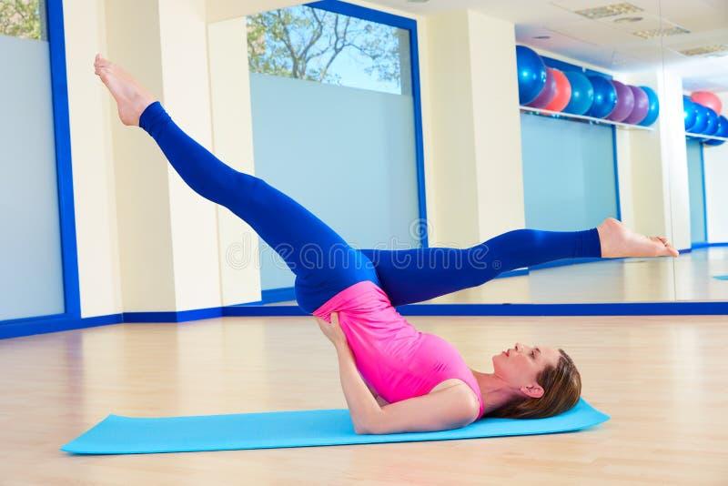 Den Pilates kvinnan scissor övningsgenomkörare på idrottshallen arkivfoton
