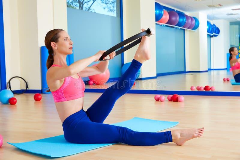 Den Pilates kvinnan scissor magisk cirkelövningsgenomkörare arkivfoto